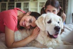 坐与爱犬的母亲和女儿在客厅 免版税图库摄影