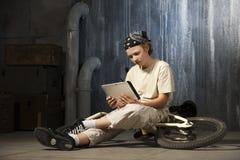 坐与片剂个人计算机的少年 库存图片