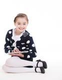 坐与片剂的逗人喜爱的小女孩画象。 免版税库存图片