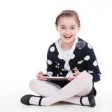 坐与片剂的逗人喜爱的小女孩画象。 免版税库存照片