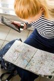 坐与片剂的镶边毛线衣的旅游白肤金发的妇女和看地图 在视图之上 库存照片