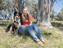 坐与狗的妇女在公园 免版税库存照片