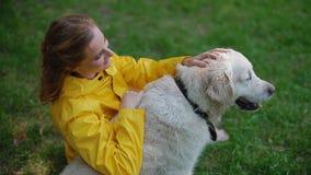 坐与狗的黄色雨衣的妇女 影视素材