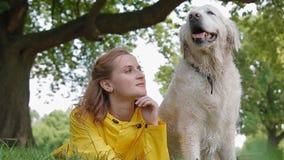 坐与狗的黄色雨衣的妇女 股票录像