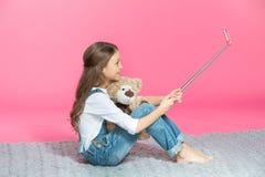 坐与玩具熊和采取的微笑的小女孩selfie 库存照片