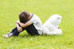 坐与玩具熊的哀伤的小男孩 转动和降下他们的头 悲伤,恐惧,失望,寂寞概念 免版税库存图片