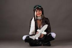 坐与玩具飞机的飞行员帽子的微笑的妇女在手上 免版税库存图片