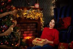 坐与礼物的怀孕的女孩在圣诞树 库存照片