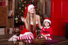 坐与礼物的逗人喜爱的女孩临近在圣诞老人服装的圣诞树,微笑和获得乐趣 Xmas大气在家 免版税库存图片