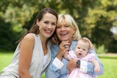 坐与祖母和孩子的微笑的母亲 免版税库存图片