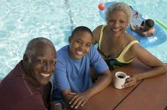 坐与祖父母的男孩(13-15)在野餐桌上由游泳池举起了看法画象。 库存图片