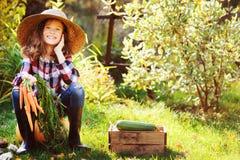 坐与秋天收获的愉快的农夫儿童女孩在庭院里 免版税库存照片