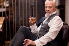 坐与科涅克白兰地玻璃和雪茄的人 库存照片