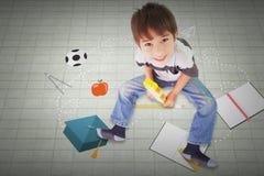 坐与积木的逗人喜爱的男孩的综合图象 免版税库存照片