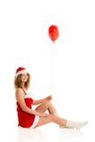 坐与红色气球垂直的圣诞老人女孩 图库摄影
