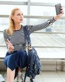 坐与背包的镶边毛线衣的旅游白肤金发的妇女和在驻地或终端做selfie 免版税库存图片