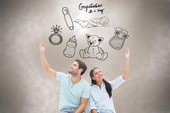 坐与胳膊的逗人喜爱的夫妇的综合图象被举 免版税库存图片