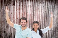 坐与胳膊的逗人喜爱的夫妇的综合图象被举 免版税图库摄影