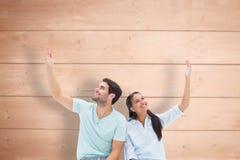 坐与胳膊的逗人喜爱的夫妇的综合图象被举 库存图片