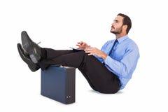 坐与脚的商人,当使用他的片剂时 图库摄影