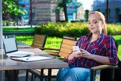 坐与膝上型计算机和巧妙的电话的十几岁的女孩在咖啡馆 免版税库存照片