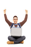 坐与膝上型计算机和打手势幸福的愉快的男学生 库存图片