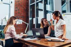 坐与膝上型计算机和文件的小组女性董事在书桌被会集谈论问题和计划在a 免版税图库摄影