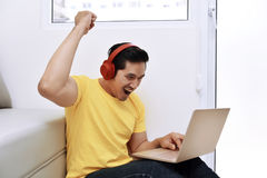 坐与膝上型计算机和耳机的愉快的亚裔人 免版税库存照片