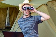 坐与膝上型计算机在帐篷附近和神色的帽子的一个年轻人通过双筒望远镜 免版税库存照片