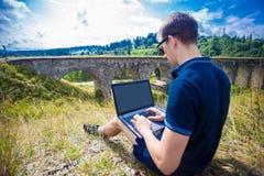 坐与膝上型计算机室外近的老石铁路桥的一个年轻人 免版税图库摄影