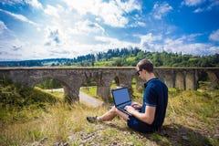 坐与膝上型计算机室外近的老石铁路桥的一个年轻人 库存照片