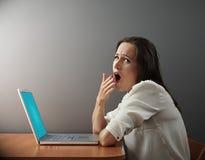 坐与膝上型计算机的乏味妇女 免版税库存图片