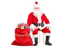 坐与袋子的圣诞老人有很多存在 免版税图库摄影