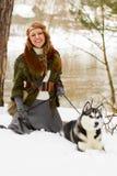 坐与西伯利亚爱斯基摩人狗的愉快的少妇 免版税库存图片