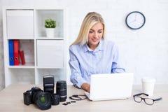 坐与计算机和摄影设备的妇女摄影师在现代办公室 免版税库存图片