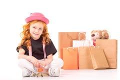 坐与购物汽车玩具的微笑的孩子 免版税库存图片