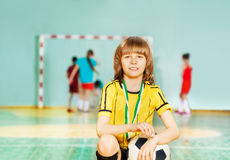 坐与足球的愉快的男孩在体育馆里 免版税图库摄影