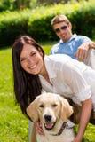 坐与金毛猎犬的夫妇在公园 库存图片