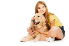 坐与金毛猎犬的微笑的十几岁的女孩 免版税库存照片