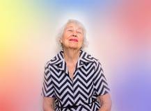 坐与闭合的眼睛的一名作的资深妇女的画象 库存图片