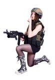 坐与攻击步枪的军事伪装的妇女 免版税图库摄影