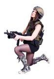 坐与攻击步枪的军事伪装的妇女 免版税库存照片