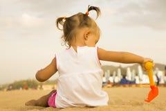 坐与他的回到照相机和使用与在沙子的玩具犁耙的美丽的婴孩在海滩 库存照片