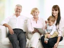 坐与他们的女儿和孙子的资深夫妇 免版税图库摄影