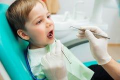 坐与嘴的男孩打开了在口头核对期间在牙医 免版税库存照片