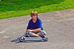坐与他的滑行车的年轻男孩 库存图片