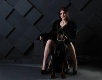 坐与黑短毛猎犬狗的美丽的时尚妇女 库存图片