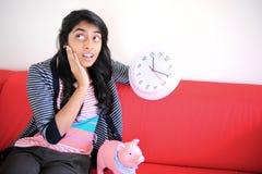 坐与piggybank的女孩拿着时钟 免版税库存照片