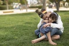 坐两个的姐妹彼此相爱 库存照片
