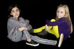 坐两个逗人喜爱的女孩偶然地看照相机 免版税库存照片